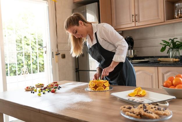 Giovane pasticcere che cucina una torta all'arancia con le arance a fette