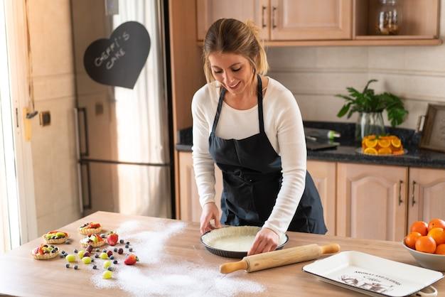 Giovane pasticcere che cucina una torta dolce in cucina