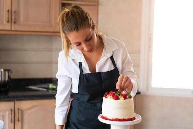 Giovane pasticcere che cucina una torta di velluto rosso tradizionale in cucina