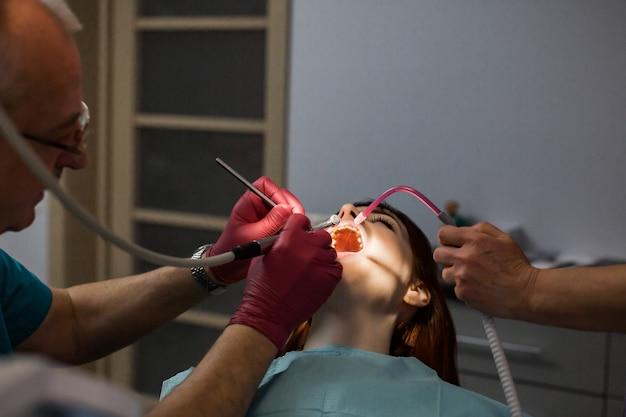 La giovane donna paziente nell'ufficio del dentista fa controllare e trattare i denti con gli strumenti dentali dal dentista maschio senior e dall'assistente femminile. concetto di trattamento odontoiatrico