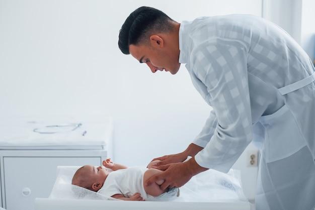 Il giovane pediatra è con il piccolo bambino nella clinica durante il giorno.
