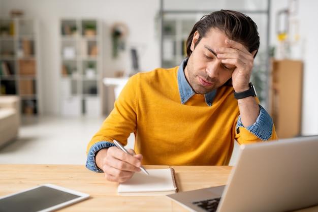 Giovane uomo d'affari pensieroso con la penna che si siede dallo scrittorio e che si piega sopra la pagina vuota del blocco note mentre lavorava davanti al computer portatile