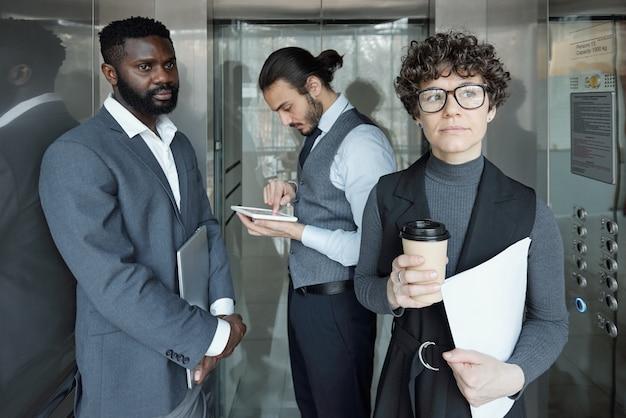 Giovane imprenditrice pensierosa con un bicchiere di caffè e carta in movimento in ascensore con due uomini interculturali