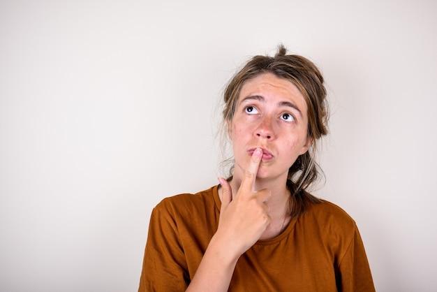 Giovane donna pensierosa in una maglietta marrone ha messo il dito sul viso isolato. concetto per idee o riflessioni.