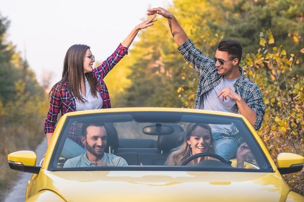 I giovani viaggiano su una cabriolet gialla