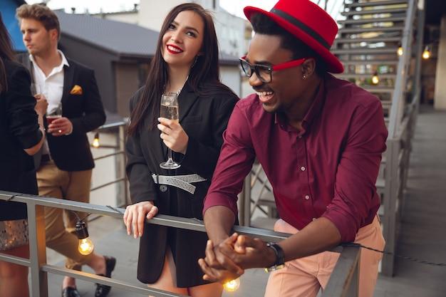 I giovani festeggiano, sembrano felici, fanno festa in ufficio o al bar. uomini e donne che bevono alcolici, parlano, ridono. vacanze, fine settimana, affari e finanza, concetto di amicizia. costruzione di squadra.