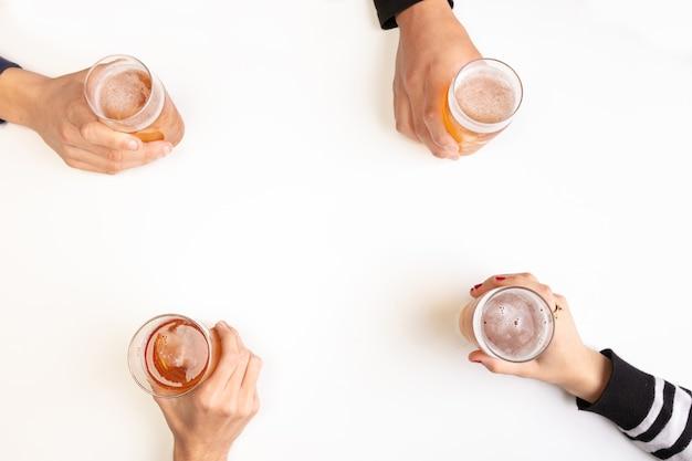 I giovani bevono birre e si divertono su un tavolo bianco