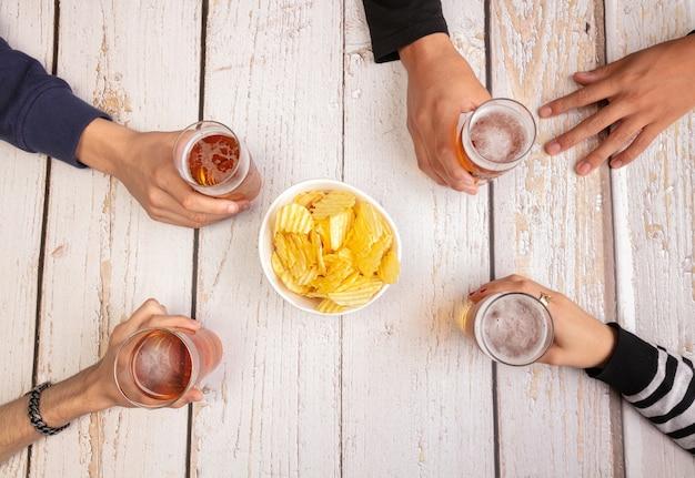 Giovani che bevono birra e si divertono su un tavolo di legno