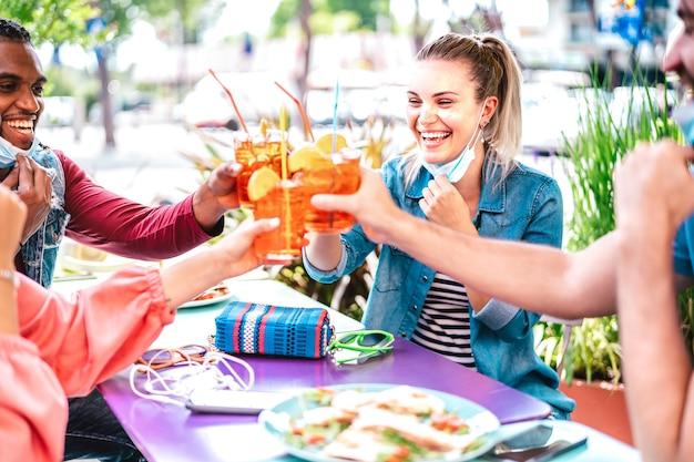 Giovani che bevono spritz al cocktail bar che indossano maschere per il viso