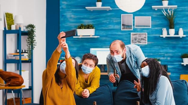 Giovani di culture diverse che si fanno selfie indossando maschere di protezione che si divertono insieme durante la nuova festa normale mantenendo le distanze sociali, tenendo in mano bottiglie di birra godendosi il tempo in soggiorno