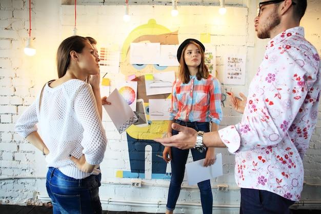 Il gruppo di giovani in un ufficio moderno ha riunioni di squadra e brainstorming mentre si lavora al laptop e si beve caffè.