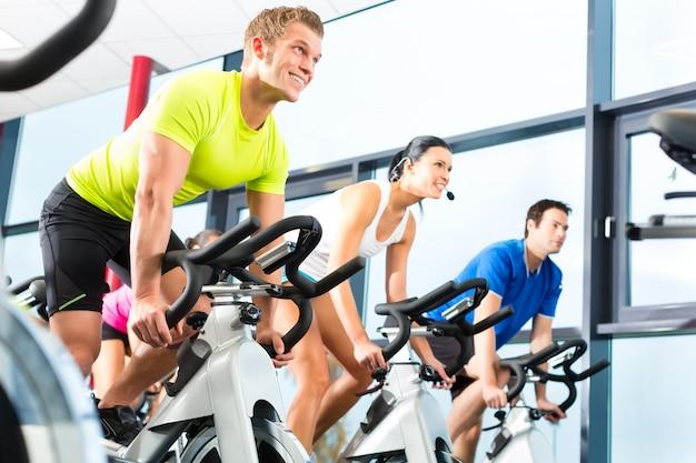 Giovani, gruppo di donne e uomini che fanno sport spinning in palestra per il fitness