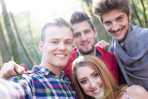 I giovani che si divertono insieme nel parco sul fiume e prendendo selfie