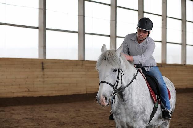 Giovani su un addestramento di cavalli in un'arena di legno