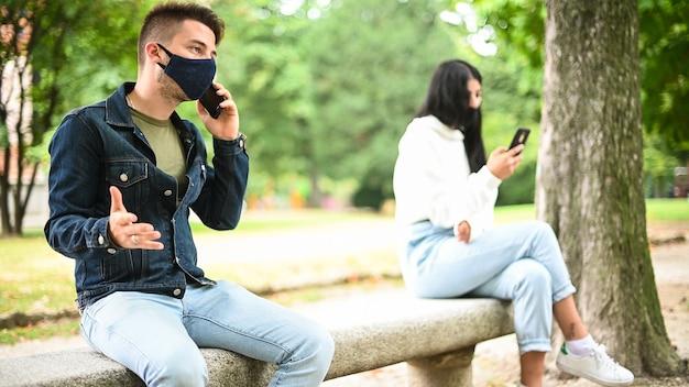 Giovani che tengono le distanze sociali a causa del coronavirus mentre usano il telefono all'aperto in un parco