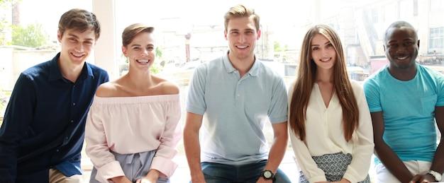 Giovani che guardano la telecamera con un sorriso mentre sono seduti in ufficio.