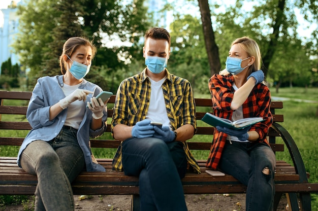 Giovani in maschere seduti su una panchina nel parco, quarantena. persona di sesso femminile che cammina durante l'epidemia, assistenza sanitaria e protezione, stile di vita pandemico