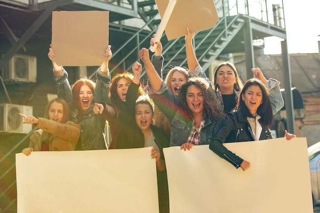 Giovani che protestano per i diritti e l'uguaglianza delle donne per strada. le donne caucasiche si incontrano per problemi sul posto di lavoro, pressioni maschili, abusi domestici, molestie. copyspace. tenendo manifesti.