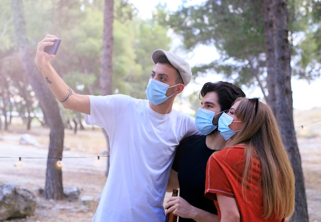 Giovani riuniti dopo la quarantena causata dalla covide19. prendi precauzioni con le maschere chirurgiche e scatta foto insieme a uno smartphone.