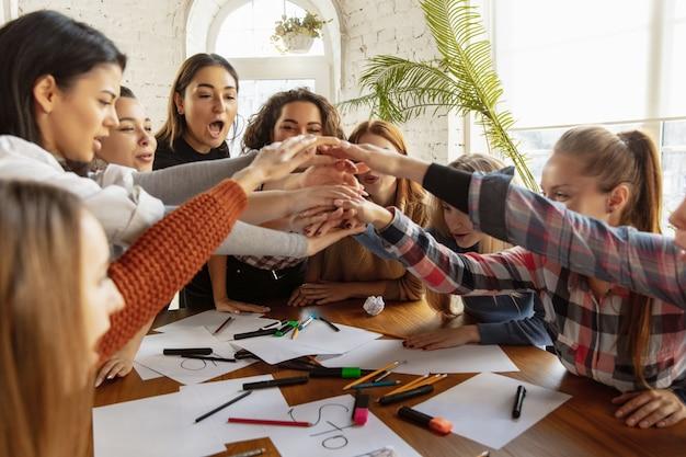 Giovani che si stringono la mano mentre discutono di diritti e uguaglianza delle donne in ufficio
