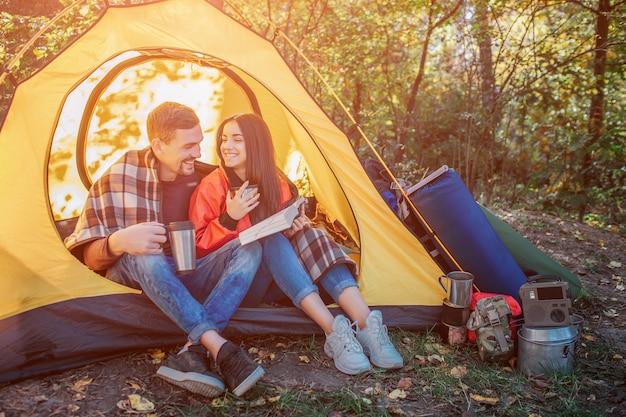I giovani seduti in tenda e si guardano l'un l'altro. tiene il libro aperto mentre il ragazzo ha il thermos in mano. tiene una termo tazza. c'è zaino con attrezzatura in tenda.
