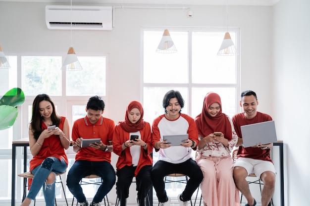 Giovani seduti insieme con il proprio gadget
