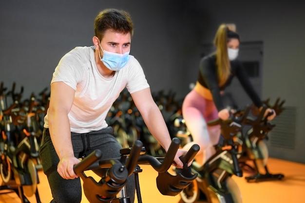 Giovani che girano in palestra con maschera protettiva durante l'epidemia di coronavirus.