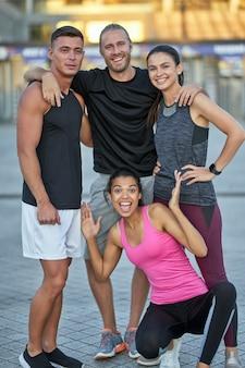 Giovani in abbigliamento sportivo in piedi insieme e sorridenti
