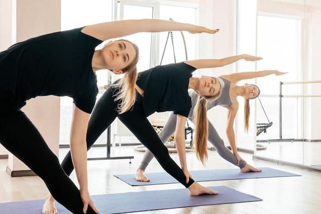 I giovani che si allungano nella classe di yoga facendo pose di yoga