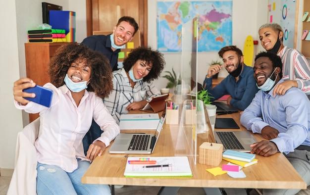 Giovani che scattano selfie all'interno dell'ufficio di coworking mentre indossano maschere protettive per la prevenzione della diffusione del coronavirus - focus sul volto della donna africana