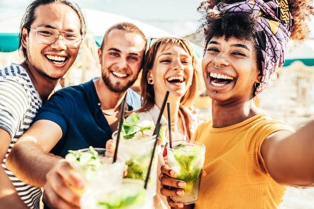 Giovani che tostano drink mojito al cocktail bar sulla spiaggia amici multirazziali felici che si divertono