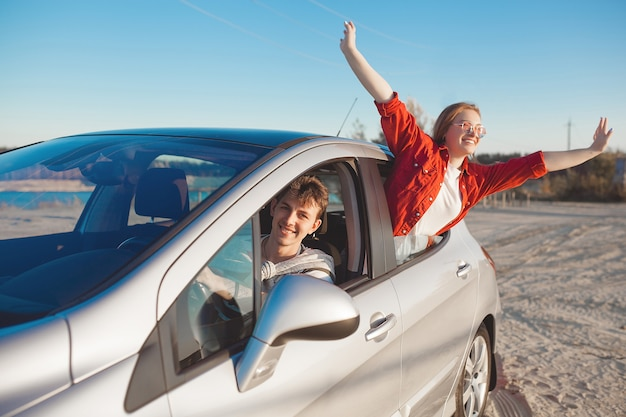 Giovani che viaggiano in macchina. coppie che hanno un viaggio in automobile.