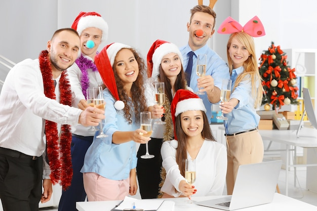 Giovani con bicchieri di champagne che celebrano il natale alla festa aziendale in ufficio