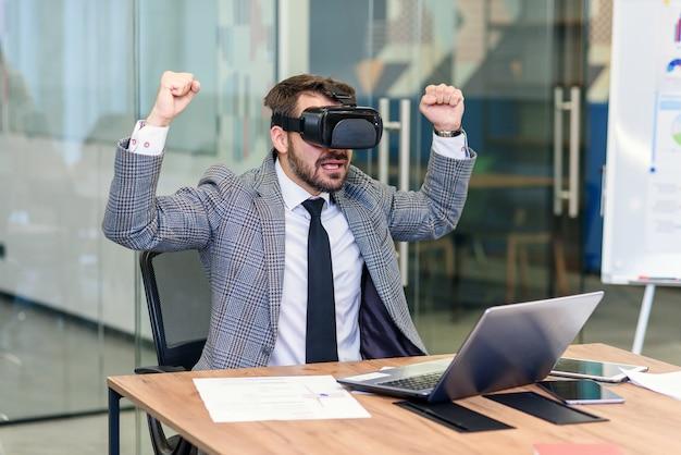 Giovani che lavorano in ufficio, creativi barbuti che provano un nuovo prodotto o giocano con occhiali per realtà virtuale