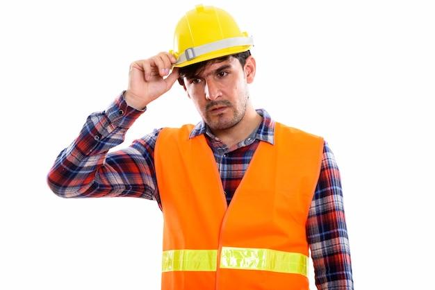 Giovane operaio edile persiano pensando mentre si tiene elmetto protettivo