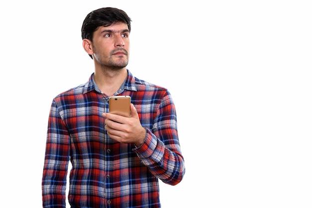 Giovane uomo persiano che tiene il telefono cellulare mentre sottile