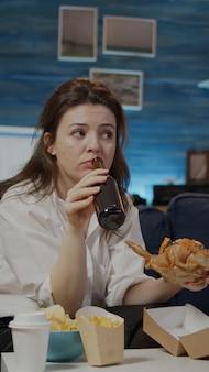 Giovane che si gode hamburger e birra da asporto dopo il lavoro seduti a casa sul divano. donna che mangia fast food e beve bevande alcoliche mentre guarda la televisione in soggiorno