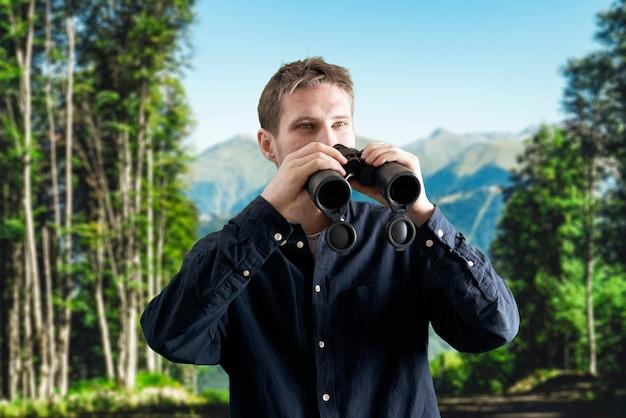 Un giovane che fa un'escursione in montagna e usa il binocolo, concetto di viaggio