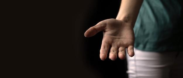 Giovane che offre una mano amica, banner gesto di invito con sfondo nero, copia spazio foto