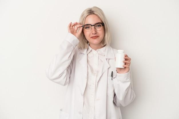 La giovane donna del farmacista che tiene le pillole isolate su fondo bianco ha eccitato mantenendo il gesto giusto sull'occhio.