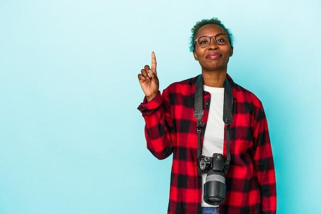 Giovane donna afroamericana del fotografo isolata su fondo blu che mostra il numero uno con il dito.