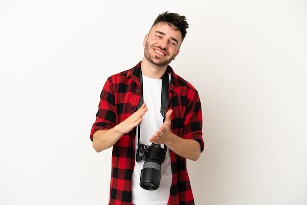 Giovane fotografo uomo caucasico isolato su sfondo bianco che applaude dopo la presentazione in una conferenza