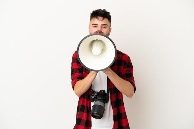 Giovane fotografo caucasico uomo isolato su sfondo bianco che grida attraverso un megafono
