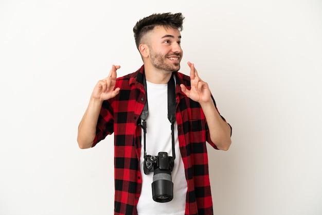 Giovane fotografo caucasico uomo isolato su sfondo bianco con le dita incrociate
