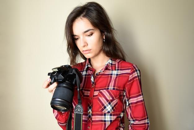 Giovane fotografo che controlla una macchina fotografica professionale