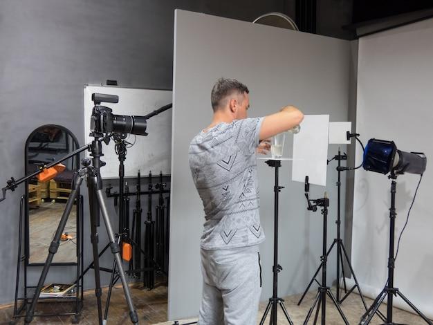 Un giovane fotografo è preparato per la fotografia in studio. fotografia involontaria