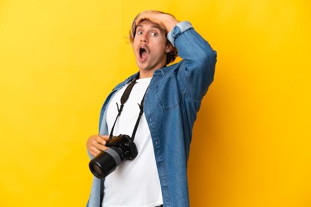 Giovane fotografo uomo isolato facendo gesto di sorpresa mentre guarda al lato