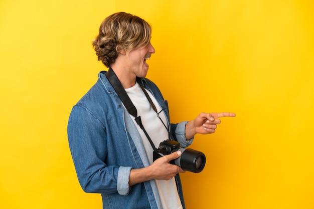 Il giovane fotografo uomo ha isolato il dito puntato di lato e presenta un prodotto