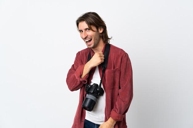 Giovane fotografo uomo isolato su bianco che celebra una vittoria