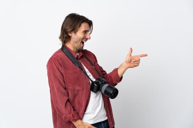 Giovane fotografo uomo isolato su bianco che punta il dito a lato e che presenta un prodotto